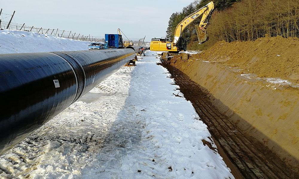 Rohr im Schnee auf Baustelle mit Bagger