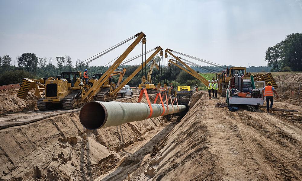 Pipelineabschnitt hängt an Baggern auf Baustelle