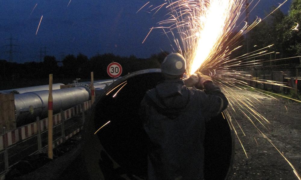Mitarbeiter schweißt am Rohr bei Nacht