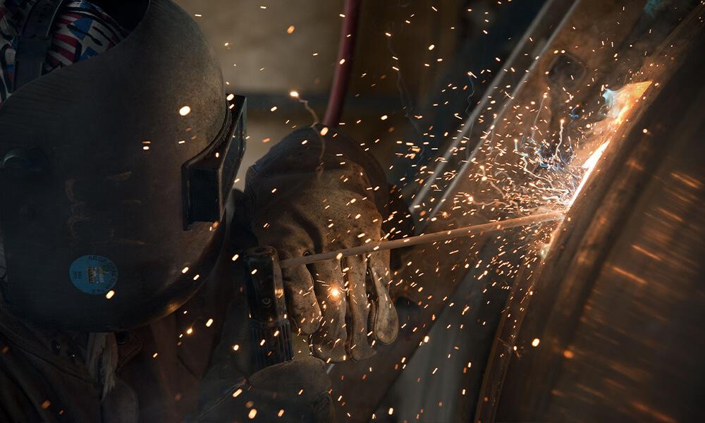 Schweißer in Werkstatt schweißt an Rohr