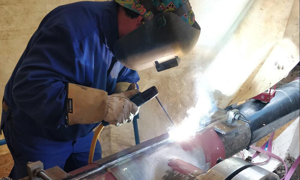 Schweißer in Schutzkleidung arbeitet am Rohr
