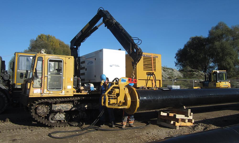 Mitarbeiter zwischen Baufahrzeugen und Rohre auf Baustelle