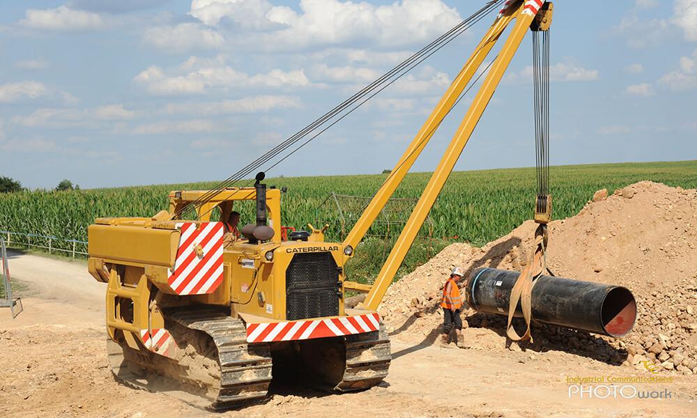 Kranmaschinen befördern Rohrabschnitt in Erde